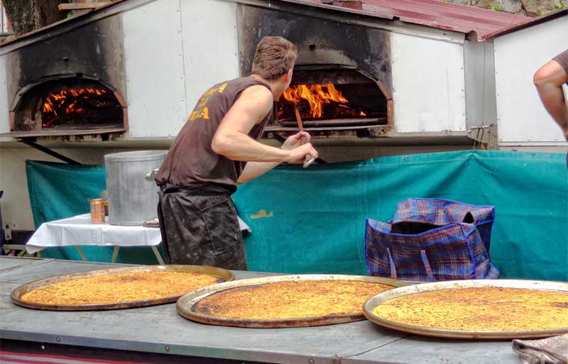 Man making socca, like pancakes made with chickpea flour, in an outdoor wood oven in Nice