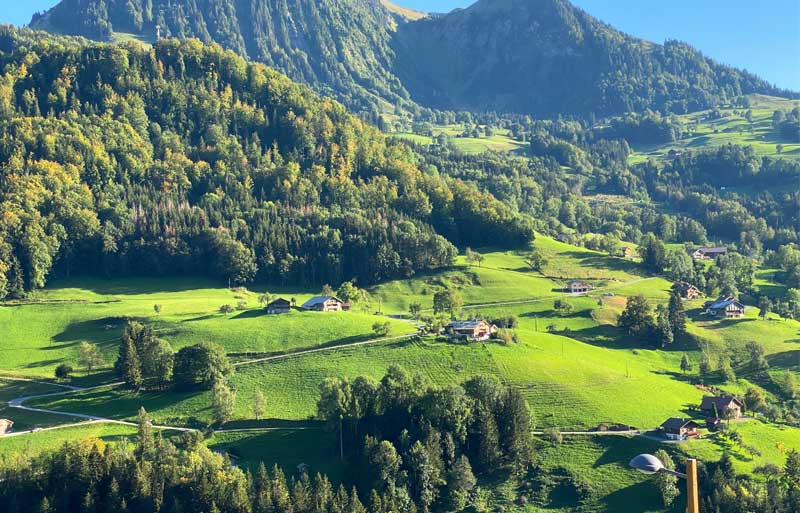 Mountains and forests dotted with alpine cottages in Manigod
