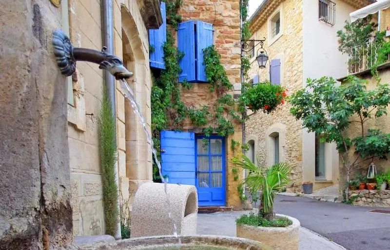 Pretty cobbled street in Gigondas, Provence, tubs filled with flowers, a small wall fountain