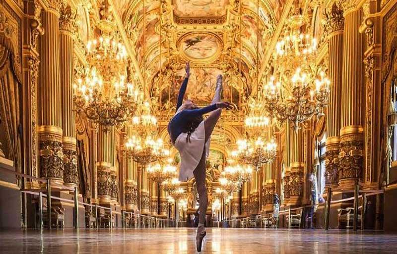 Ballet dancer stands on tiptoe in a gilded hall at the Opera Garnier Paris