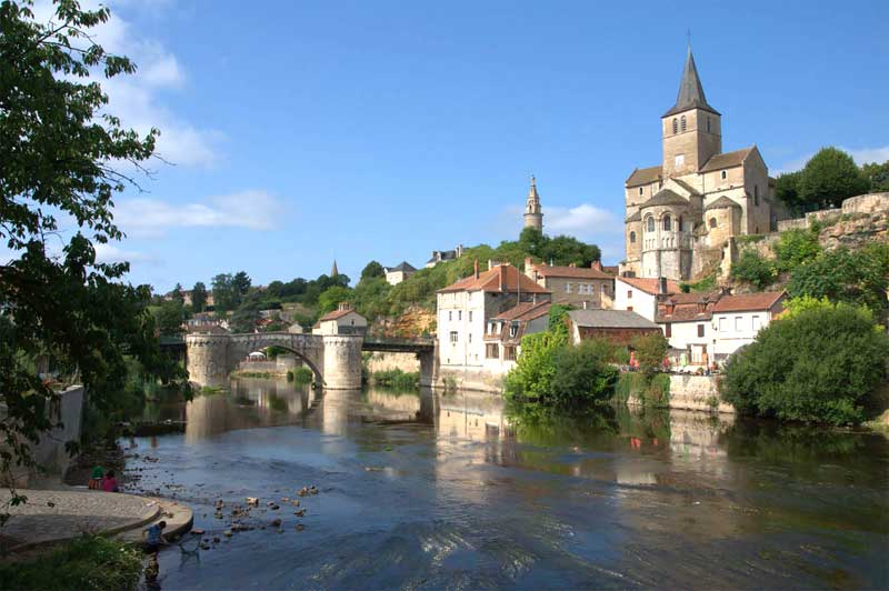 Stone bridge over a river, town of ancient stone buildings topped by an abbey at the side of the river