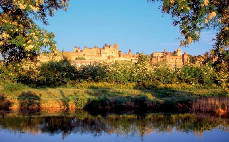 Walled city of Carcassonne seen from the Canal du Midi, its towers and turrets perched on a hill