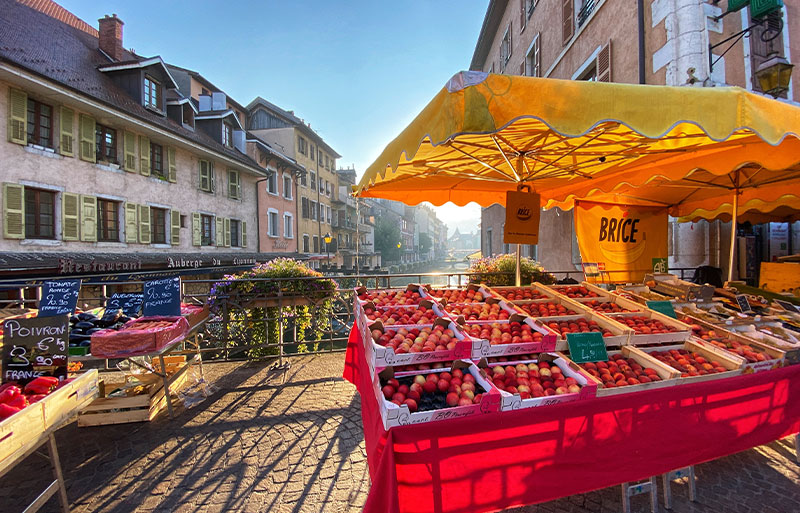 Fruit stall at a market on a cobbled bridge over a canal in Annecy