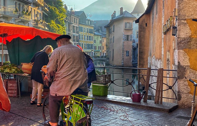Man wearing a beret, riding a bike across a cobbled bridge in Annecy