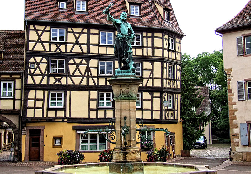 Fountain Schwendi, Colmar topped by a statue of a man holding a bunch of grapes