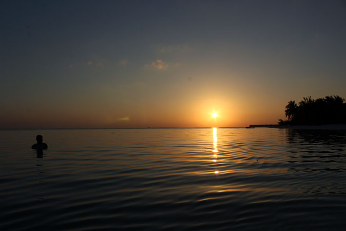 The sun descends into the calm waters off Thinnakara - beach pictures from around the world