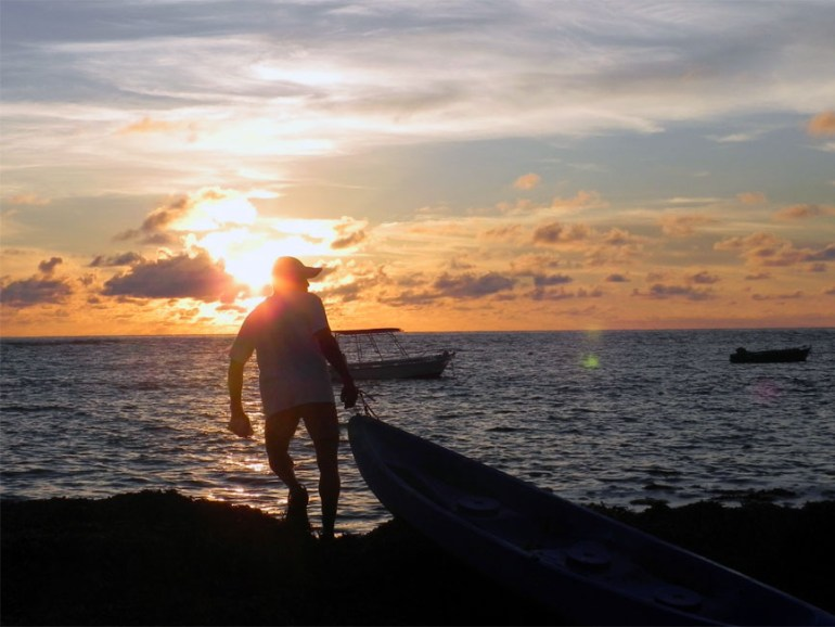 Robbie the conservationist drags a dinghy into the water for a morning of dolphin-watching on Bird Island