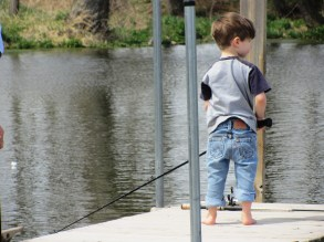 Grandpa is a big help to this little fisherman.