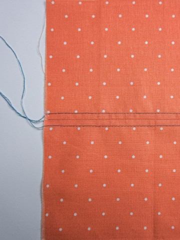 Peach coloured fabric with teal top stitching done in 2 rows.