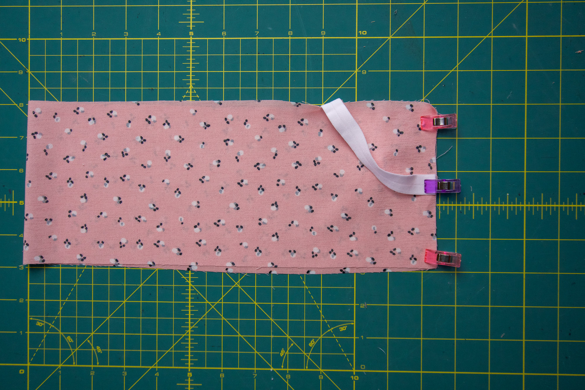 Fabric folded right sides together with an elastic loop secured on the end.