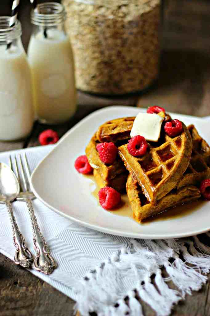 Angle shot of pumpkin spice waffles on a white plate topped with butter and raspberries.