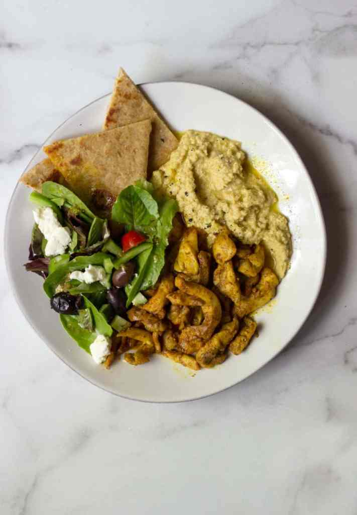 Hummus and Chicken Shawarma in a white plate with pita and greens