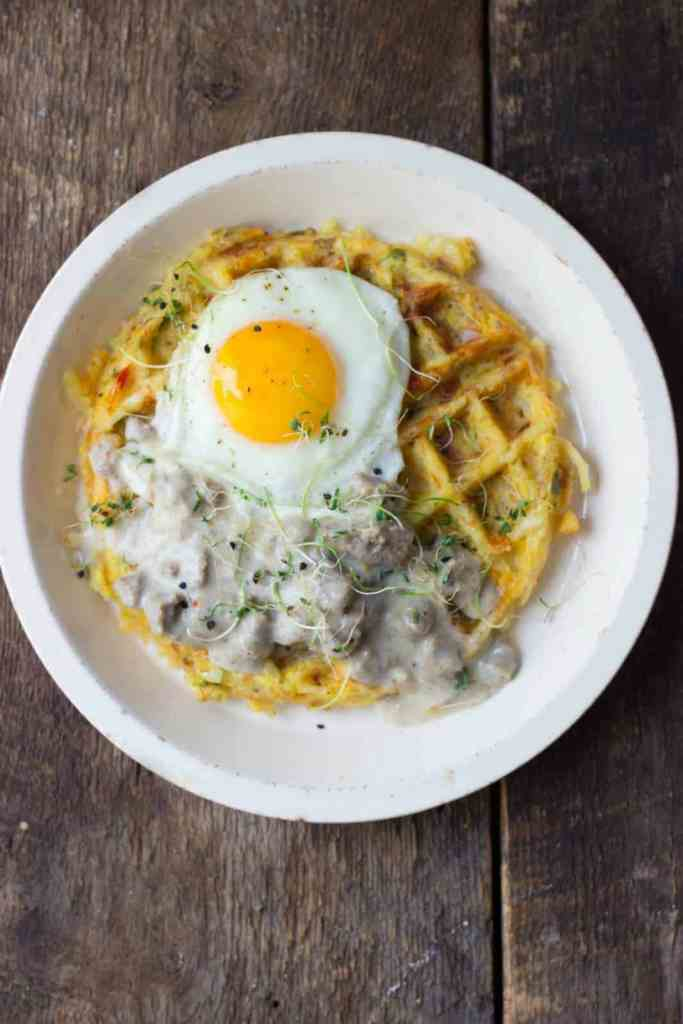 Hash brown waffle with fried egg on a white plate