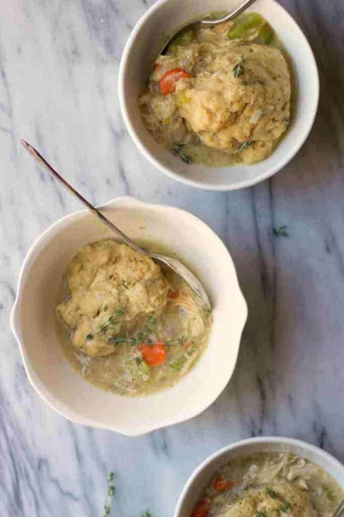Chicken and dumpling soup in white bowls.