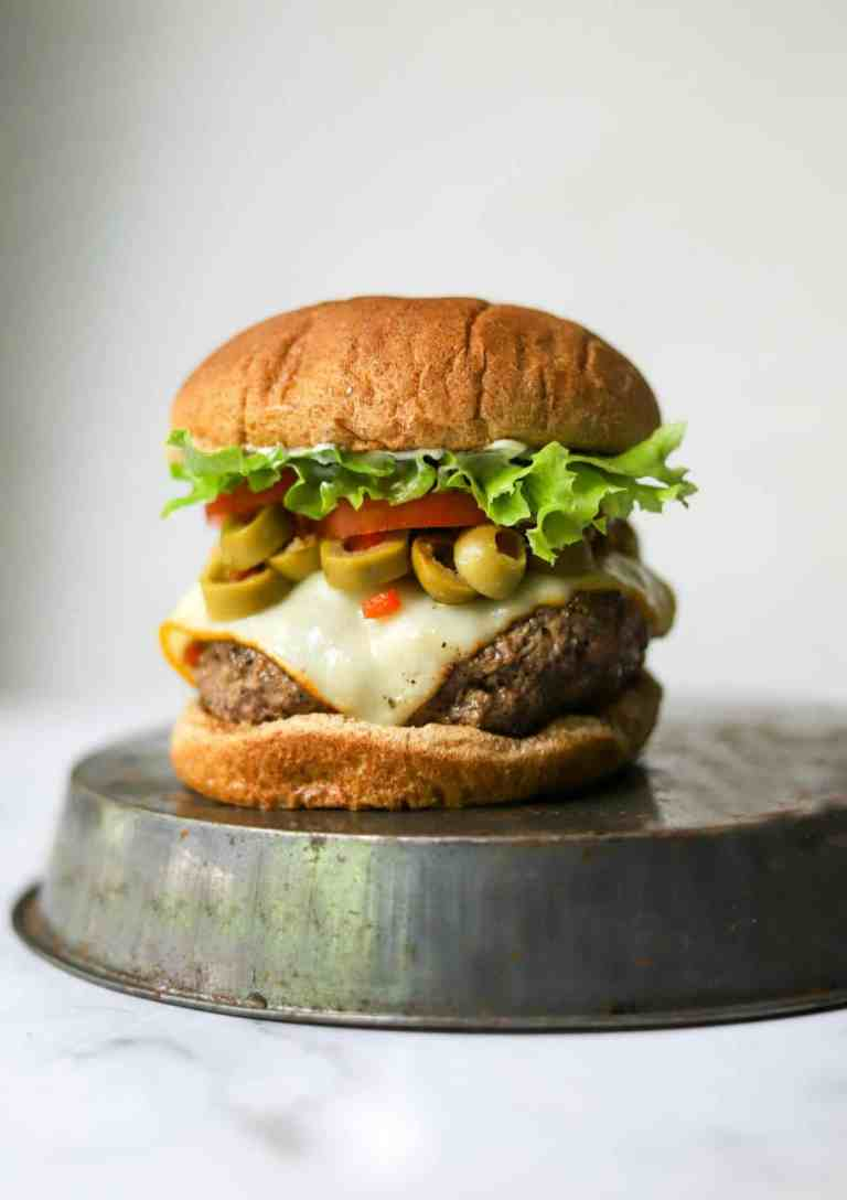 Cheesy olive burgers on a tin
