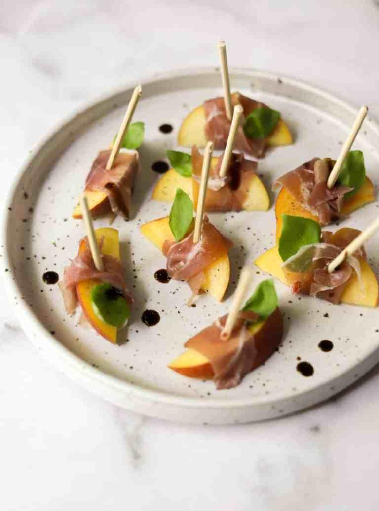 Peach prosciutto bites on a stone plate