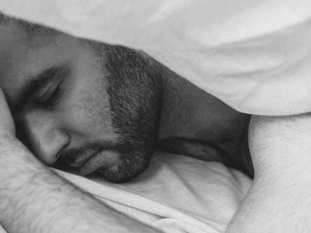 serene man sleeping under blanket