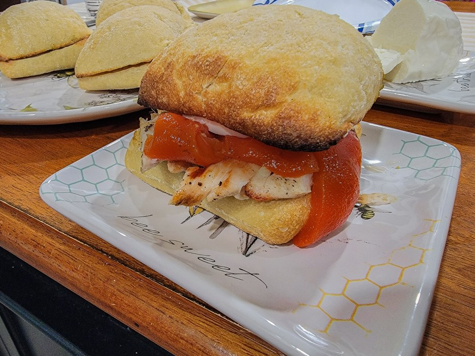 The Best Chicken Ciabatta Sandwich: A Kickass, Easy Recipe A long time ago, I worked at a hospital in a really high-end area of New York. In that hospital were two top-tier sandwich shops under the same name, and they had the best chicken ciabatta sandwich with roasted red peppers, mozzarella, and pesto. I ate it like three times a week, which was a problem because it cost more than my hourly rate at that time. So I came up with my own kickass, easy chicken ciabatta sandwich recipe, and I've been enjoying it ever since. This chicken ciabatta sandwich is so easy that you'll have no problem impressing your wife, girlfriend, date, or whoever else you choose to spend your time with. It takes like half an hour to make, including the time it takes to grill the chicken. Chicken Ciabatta Sandwich Ingredients Here are the basics of what you'll need: 1 TBSP butter 1 TBSP garlic Ciabatta rolls Thinly sliced chicken breast (one per sandwich is usually plenty) A jar of roasted red peppers Fresh mozzarella A jar of pesto Salt and pepper Balsamic vinegar How to make the easiest chicken ciabatta sandwich Guys, as long as you know how to grill a piece of chicken, you got this. Step 1: Prepare the chicken, ciabatta, and the grill Place the butter in a microwave-safe bowl and warm it until just melted. This is usually just 20 seconds or so. Once melted, mix the garlic into the butter and let sit for a few minutes. This is enough garlic butter for four rolls, so you might need more if you're making more sandwiches. While the garlic and butter are making friends, slice open your ciabatta rolls. When you're done slicing them open, spread the butter and garlic on both cut sides of each roll. Prepare the chicken by separating the cutlets and drying them with paper towels. This is an important step that some guys might not think about when preparing meat, but it ensures the seasoning sticks. Once patted dry, sprinkle each piece of chicken with salt and pepper, front and back, according to y