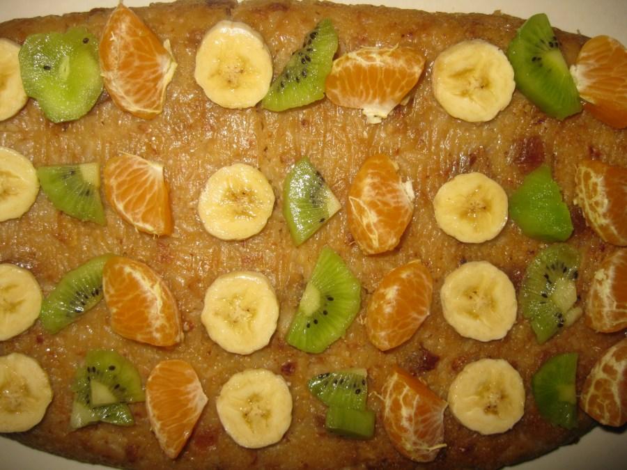 Врело изручите на плато да вам та корица буде доле. Сачекајте пола сата да се мало прохлади колач па додајте сецкано воће. Киви, поморанџу и банану.