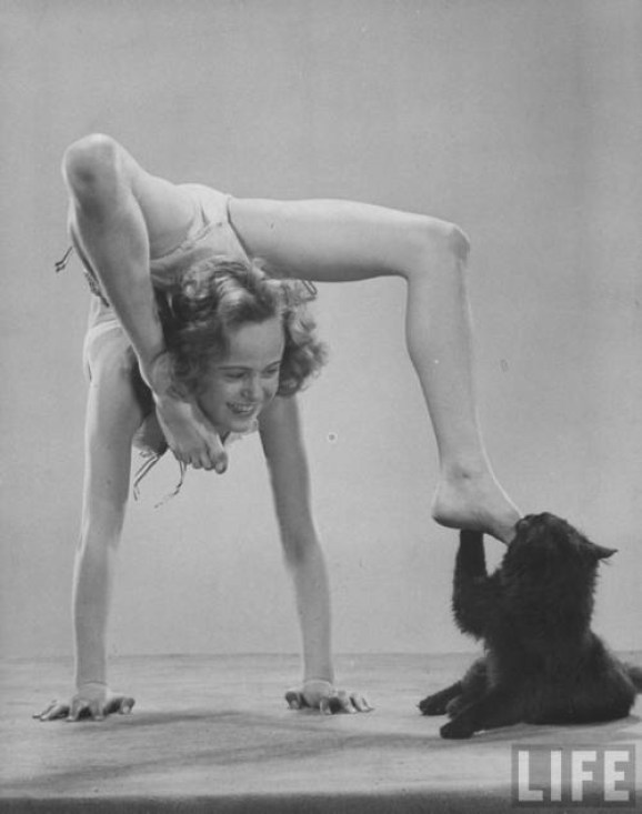 Gjon Mili's cat Blackie nibbling young acrobat's foot as she does a handstand 1943