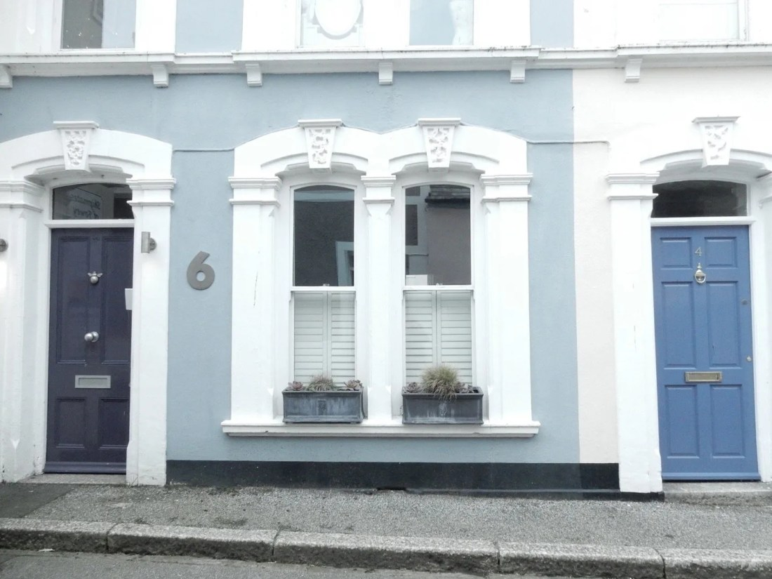 The front of a house with 2 blue doors