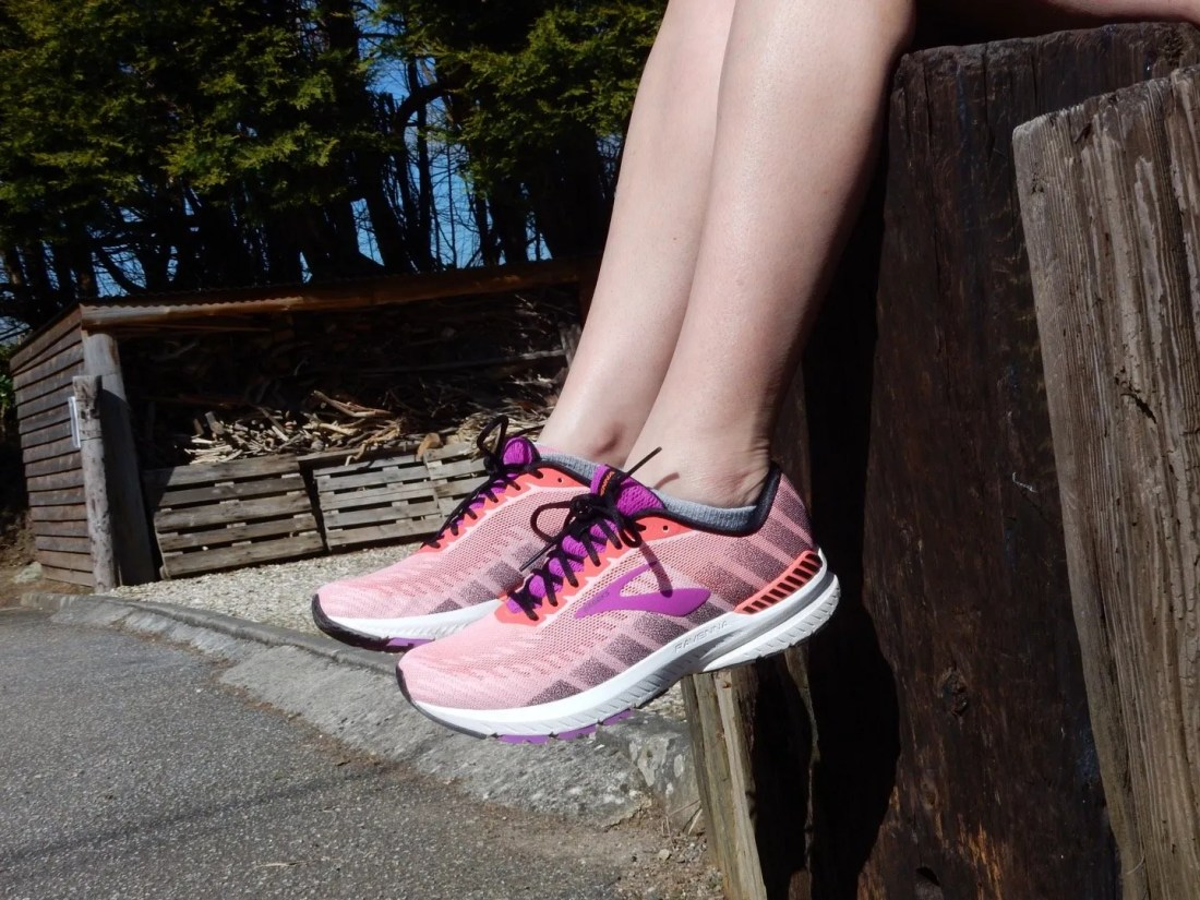 Legs dangling pink running trainers