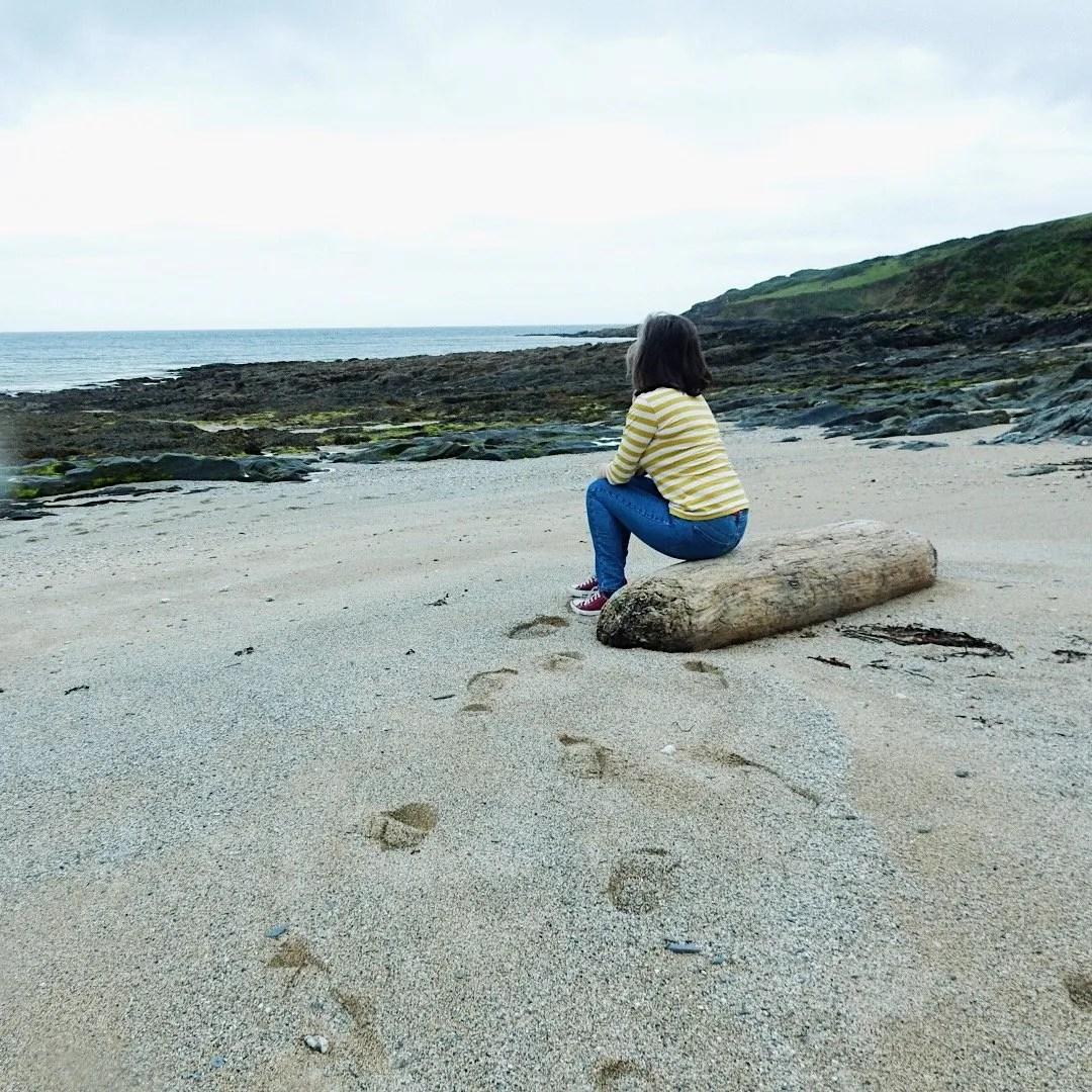 Lady Sat on Log on Beach Towan Cornwall