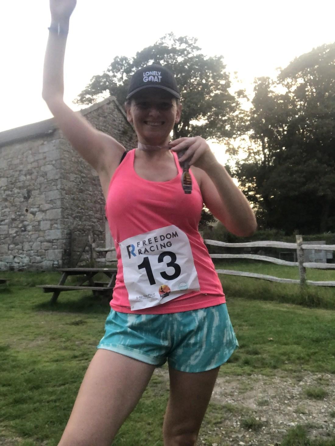 Woman runner holding medal