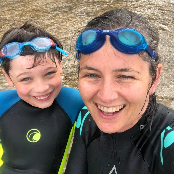 Mother and son wetsuits laughing