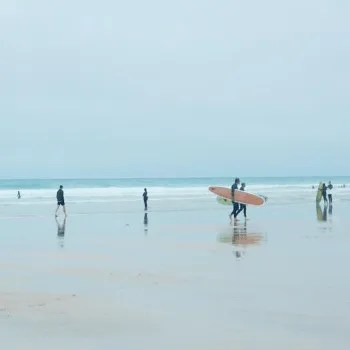 People with surfboards on Fistral Beach Cornwall