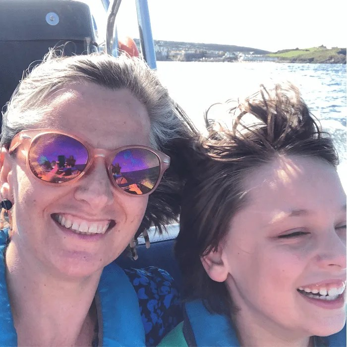 Penny Bedford smiling with her son on a rib ride