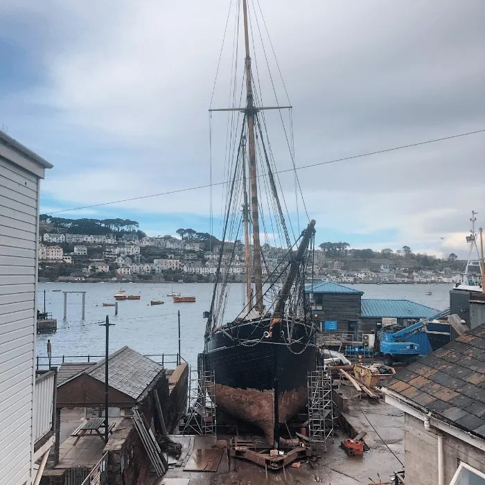 A tall boat resting in a working ship yard with Fowey in the background