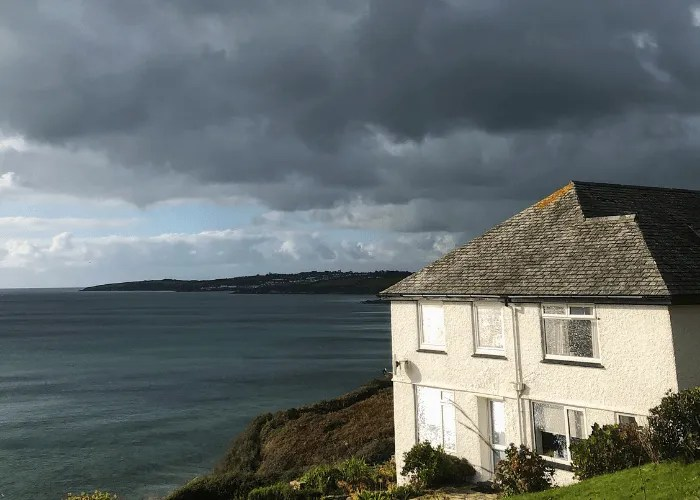 A white house overlooking the sea with stormy skies