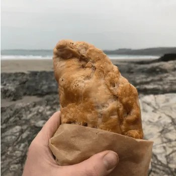 A cornish pasty in brown paper being held up on the beach