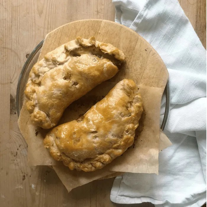 Two cooked Cornish Pasties on a chopping board