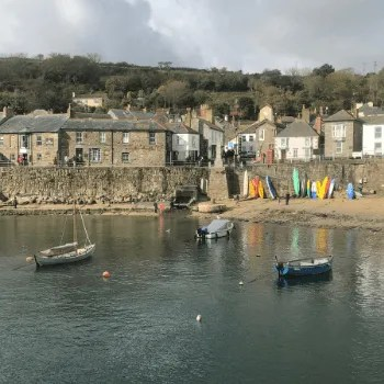Mousehole Village along the seafront with colourful kayaks and boats