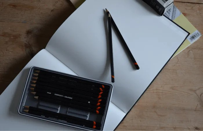 an open sketchbook with pencils and willow