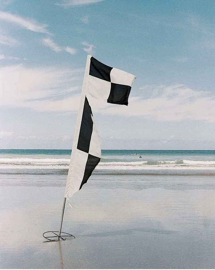 black and white flags on a Cornish beach, Newquay