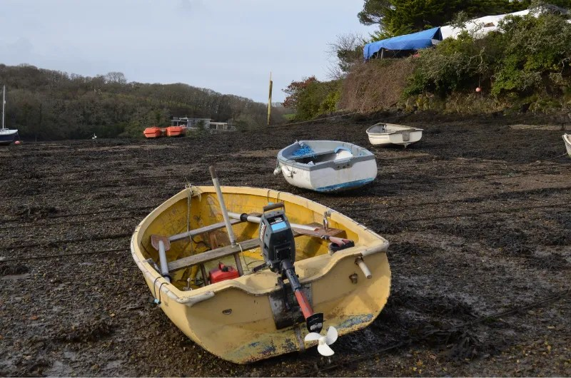 A yellow boat on the muddy banks at Percuil