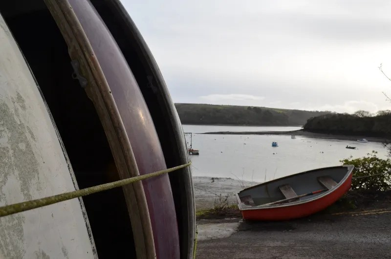 A stack of boats with a rowing boat near water at Percuil