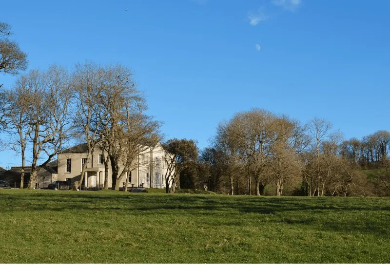 A large house with fields and trees