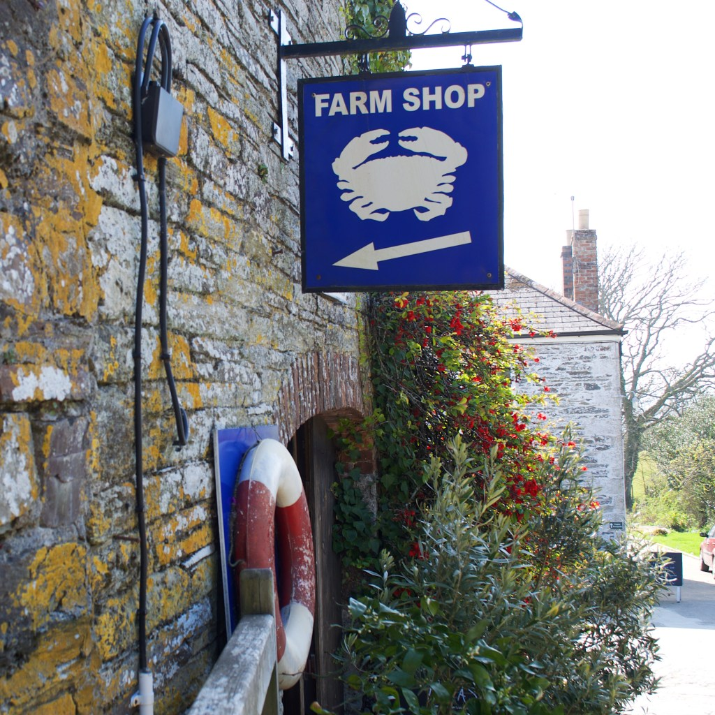 Curgurrell Farm Shop Sign hanging off the side of the building with a lifebuoy and plants