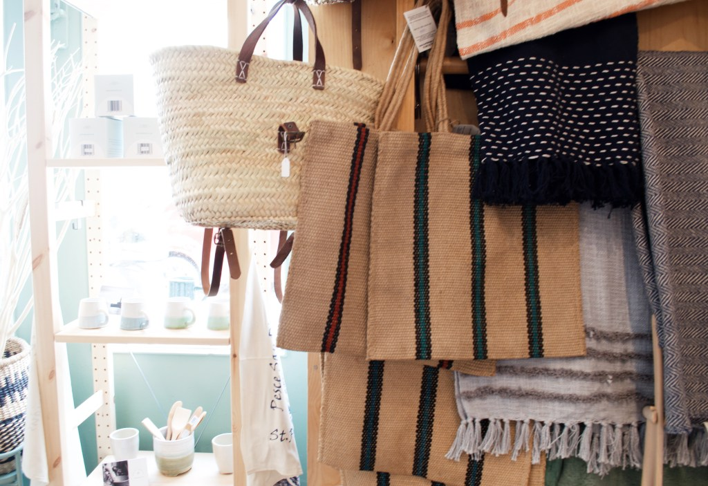 A selection of hessian and straw bags hanging up in a shop window