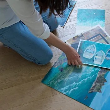 Woman reaching down to her original art on a wooden floor