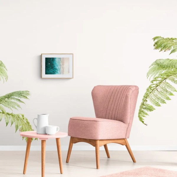 A chair and table with palm plants and a painting on the wall