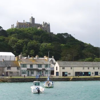2 boats in the harbour at high tide with old houses and St Michael's Mount castle in the background