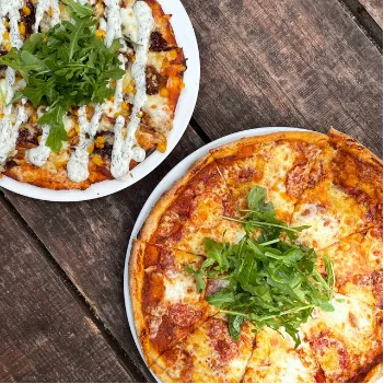 two pizzas on white plates on a picnic table