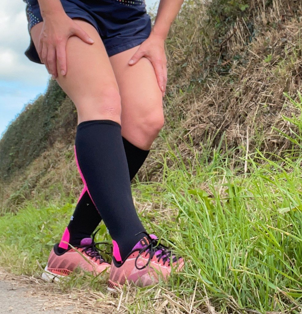 a woman's legs in knee high compression socks with pink trainers on