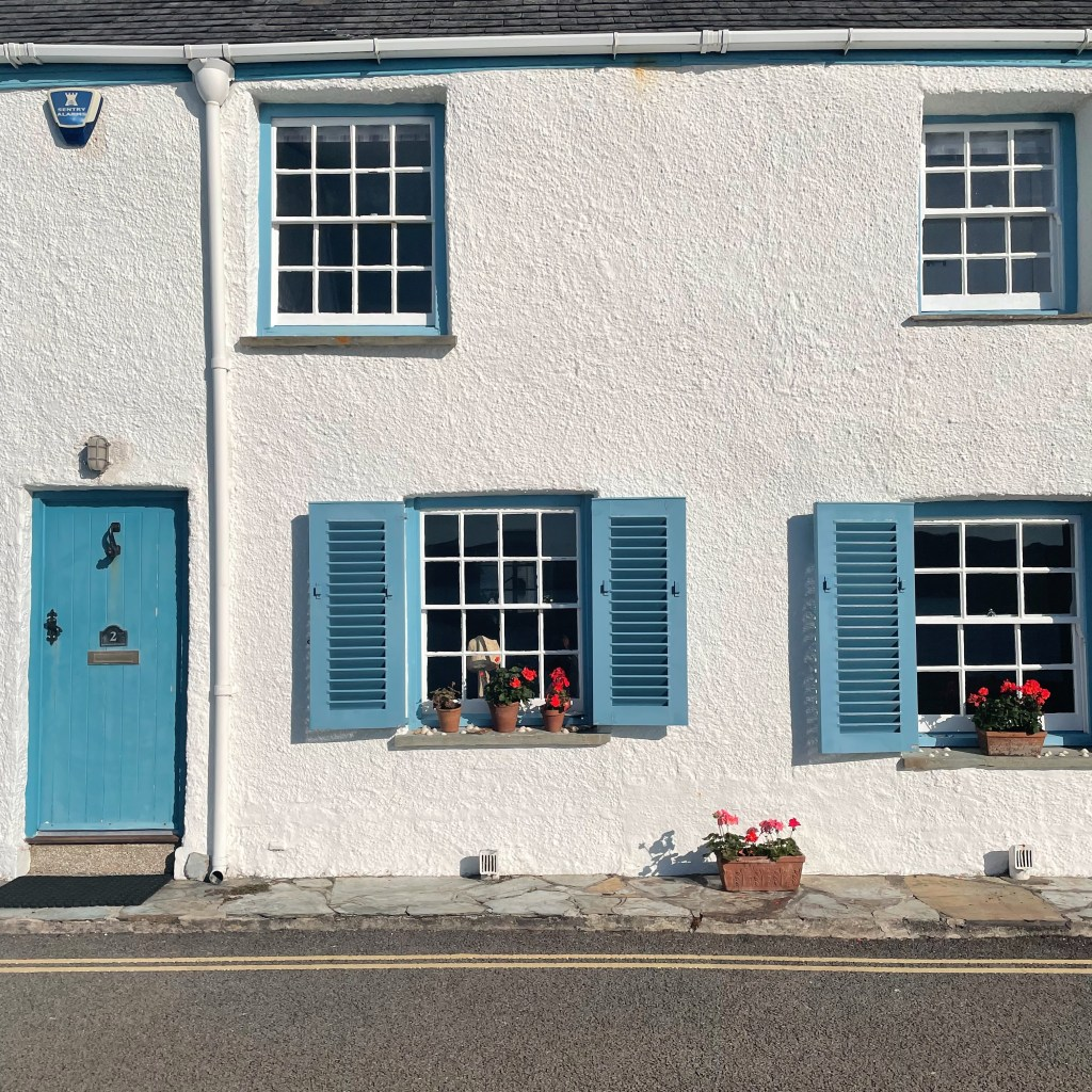 a white Cornish cottage with blue shutters and door found on during some microadventures