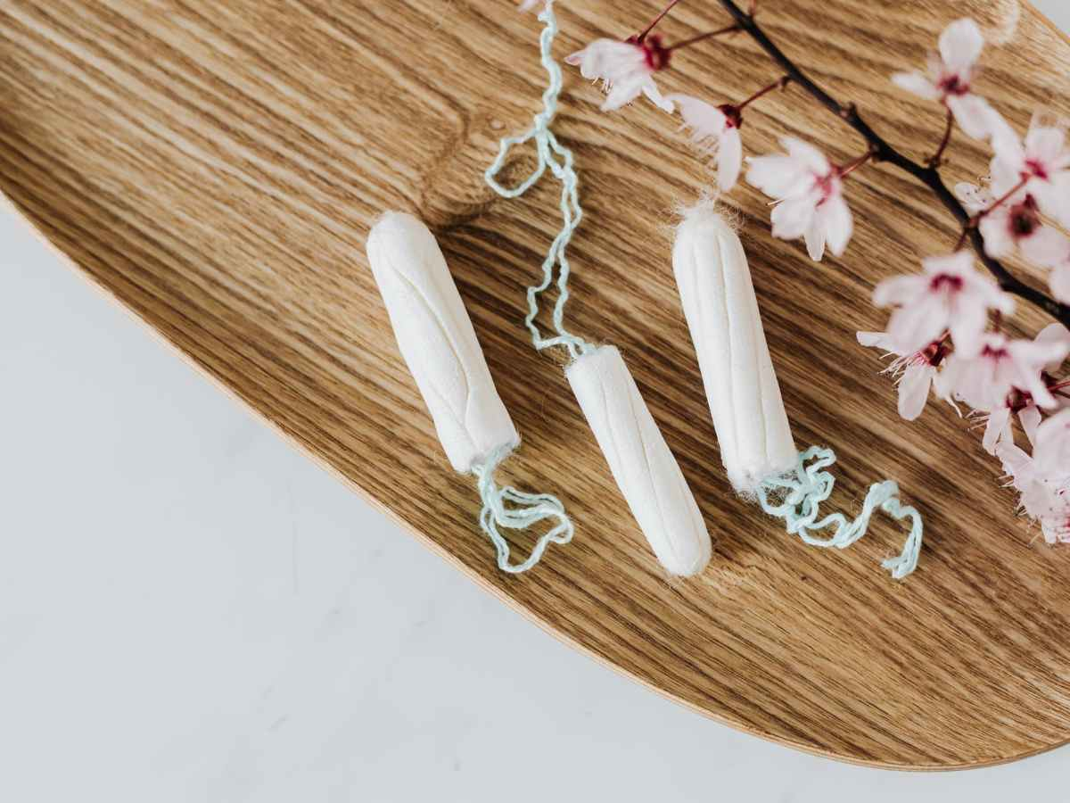 cotton menstrual tampons and delicate flower branch on wooden board
